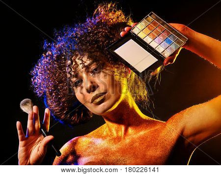 Woman with decorative cosmetics. Girl with curls holds eye shadow and brush on dark background. Golden powder on female bare shoulders.
