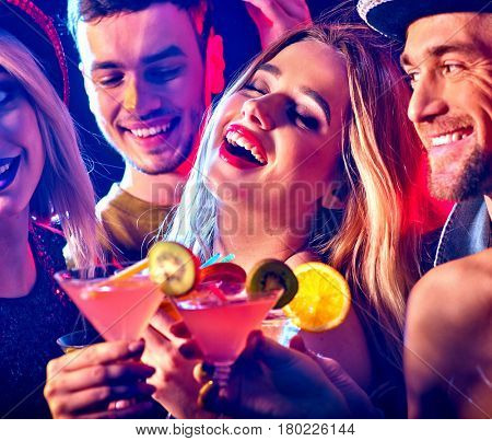 Cocktail party with group people dancing and drink cocktail. Women and men have fun in night club. Happy girl with alcohol drink on foreground.