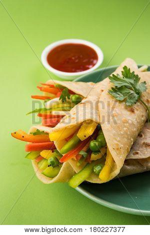 Indian popular snack food called Vegetable spring rolls or veg franky made using vegetables wrapped inside paratha/chapati/roti with tomato ketchup.