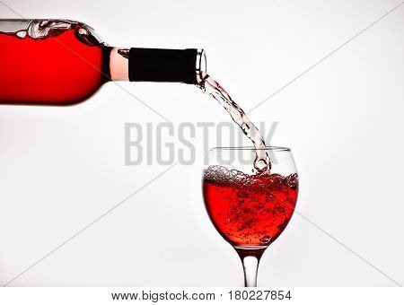 A bottle of pink wine pours into the glass. Spray of rose wine