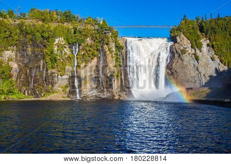 Magnificent rainbow in the waterfall Montmorency in Montmorency Falls Park, in Quebec.  Above the waterfall built bridge for walking. The concept of active and cultural tourism