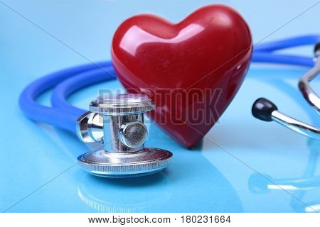 Medical stethoscope and red heart isolated on blue mirror background