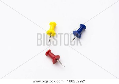 Three colored push pins on white background