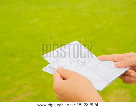 hands holding saving account passbook book bank on the green grass background