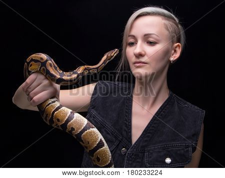 Portrait of blond woman holding snake on black background