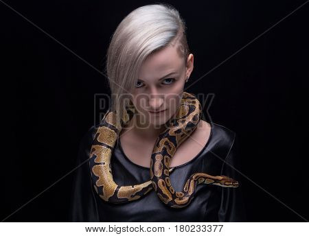 Woman in leather dress and ball python on black background
