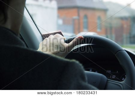 Male driver hands holding steering wheel. Driving safety in the city.