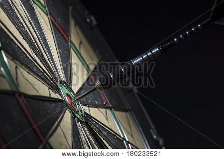 Dart in bulls eye of dartboard close up