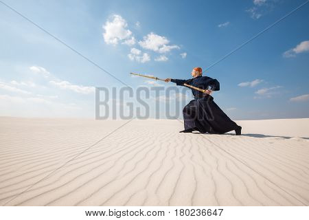 Man In Traditional Clothes Makes A Powerful Lunge With A Training Sword