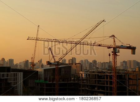 Construction cranes keep moving under the golden after sunset sky, Bangkok, Thailand