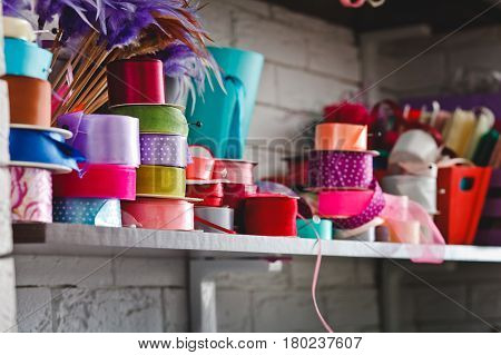 a lot of multicolored rolls with ribbons on the shelves