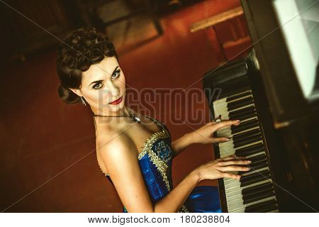 Young girl in old fashioned dress playing piano and drinking wine under candlelight in romantic vintage room.