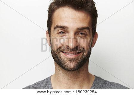 Man with stubble smiling in studio studio shot
