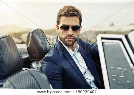 Serious man suited in sports car portrait