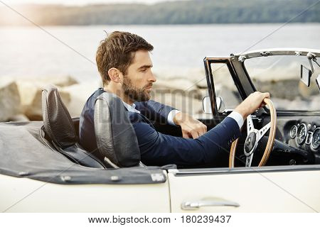 Dude in vintage sports car wearing suit