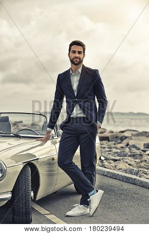 Cool guy with sports car on road portrait