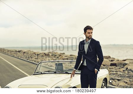 Suited dude with vintage car on road looking away