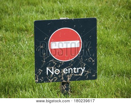 No entry warning sign covered in freshly cut grass