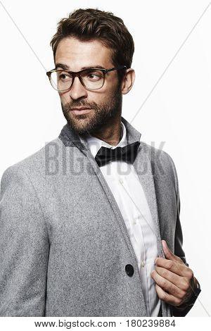 Man in bow tie and smart coat looking away