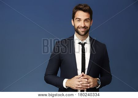 welldressed Businessman smiling in blue studio shot