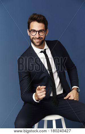 Cheeky Pointing businessman in blue studio portraitshot