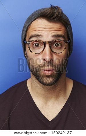 Surprised guy in hat and spectacles portrait