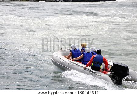 People in the boat are rafting down a mountain river.