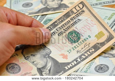 Man hand holding ten dollar banknote, saving money
