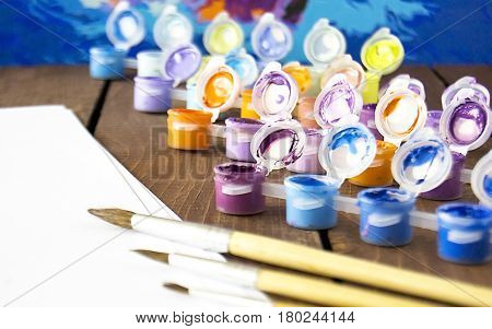 Drawing paint tassels on a wooden table painting Paints in jars. Selective focus