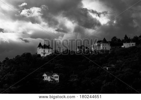 Early fall landscape with pre-stormy sky and new houses in Crimean Mountains Ukraine - black and white obscure version.