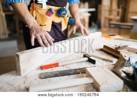 Close-up shot of male hands examining surface of wooden board, hammers, planes and saw lying on table