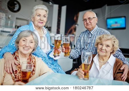 Four senior friends hanging out in pub: they sitting at table with beer glasses and posing for photography, one of them looking away thoughtfully