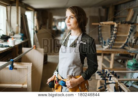 Attractive young carpenter with slight smile looking out window while standing in spacious workshop