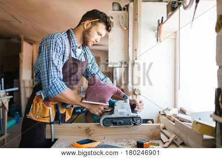 Young bearded carpenter in apron sanding plank in workshop, workbench covered with shavings