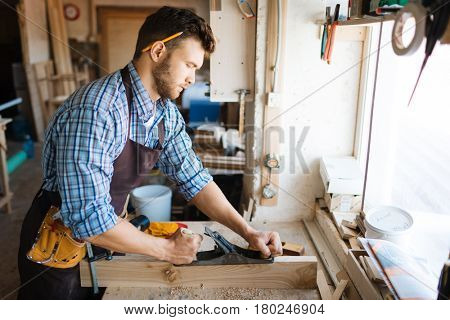 Skillful bearded woodworker in checked shirt smoothing plank with jointer plane, shavings scattered on table