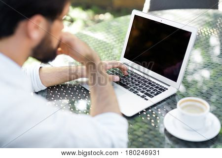 Bearded financial manager with rolled up shirt sleeves searching mistake in his calculations on laptop while drinking coffee in outdoor cafe, over shoulder view