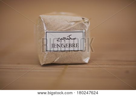 Ground ginger texture. Ginger on wooden background. Healthy food. Ginger powder background. Closeup view of ginger package. Spices of the world.