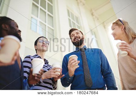 Waist-up portrait of cheerful young businessman standing outdoors with paper cup of coffee and entertaining colleagues with small talk, low angle view