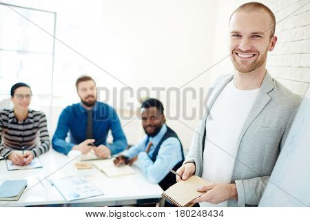 Portrait of cheerful young businessman in casualwear with pen and notebook in hands looking at camera while leading business meeting for his subordinates