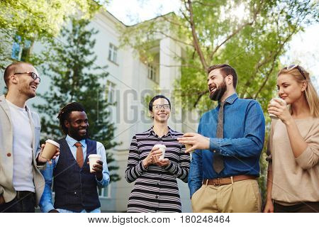 Portrait of handsome bearded businessman telling his colleagues funny story while having coffee break outdoors, low angle view