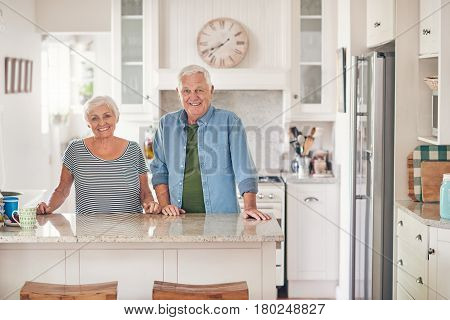Portrait of a content senior couple smiling while standing happily together in their kitchen at home
