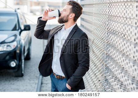 Elegant businessman standing with coffee to go near the car at the modern petrol station