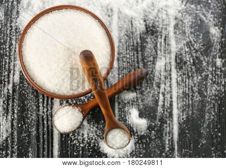 Kitchenware with white granulated sugar on black wooden background