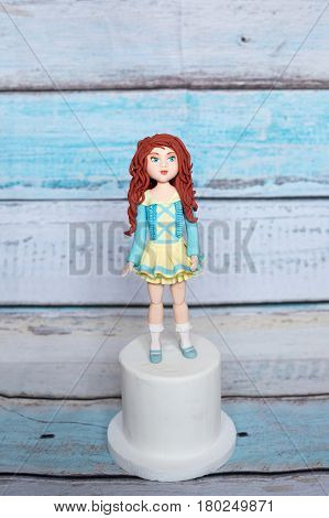 Marzipan handmade doll for cake decoration on a stand