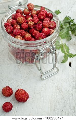Wild strawberry in glass jar with green mint leaves on white rustic wooden background with place for text. Sweet berry Fragaria for summer dessert. Healthy snack. Selective focus. Copy space.