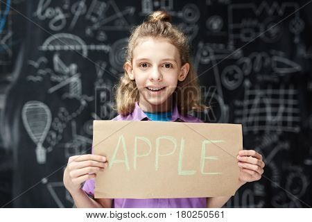 Elementary learner showing paper with written word