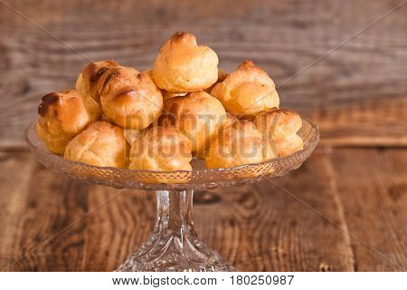 Sweet cream puffs in glass tray on wooden table.