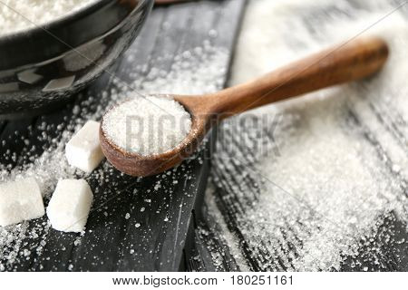 Wooden spoon with white granulated sugar on black wooden background