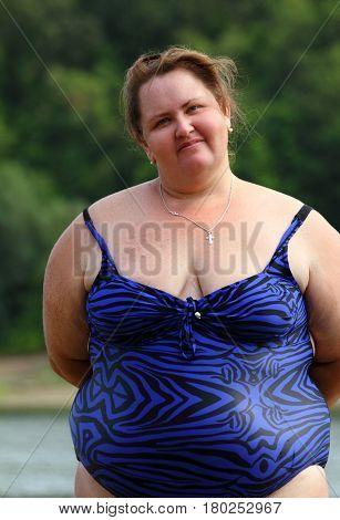 portarit of plump woman standing near river