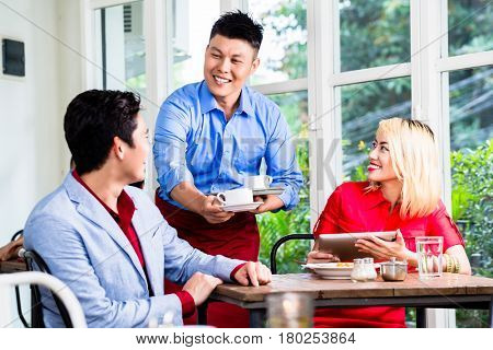 Happy Asian waiter serving a stylish couple coffee as they sit at a table in a restaurant enjoying a meal